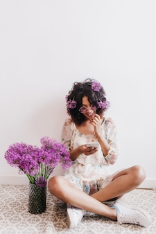 Blissful brunette girl in white sneakers posing with bouquet of alliums. indoor shot of adorable african lady sitting with legs crossed and reading phone message.