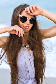 La donna castana beata indossa l'anello alla moda che ride mentre posa in mare. ritratto del primo piano della ragazza abbronzata in occhiali da sole neri che gioca con i suoi capelli scuri su sfocatura dello sfondo.