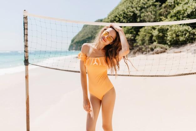 배구 세트 근처에 서있는 노란색 수영복에 행복 한 백인 여자. 모래 해변에서 자유 시간을 보내는 사랑스러운 검은 머리 아가씨의 야외 사진.