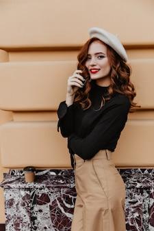 秋の日を楽しんでいるエレガントなメイクで至福の白人の女の子。フランスのベレー帽の魅力的な長髪の女性の屋外写真。