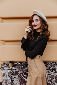 Blissful caucasian girl with elegant makeup enjoying autumn day. outdoor photo of winsome long-haired woman in french beret.