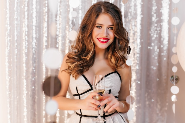 Blissful caucasian woman with trendy makeup holding wineglass and smiling. photo of fashionable lady with glass full of champagne have a good time at christmas party.