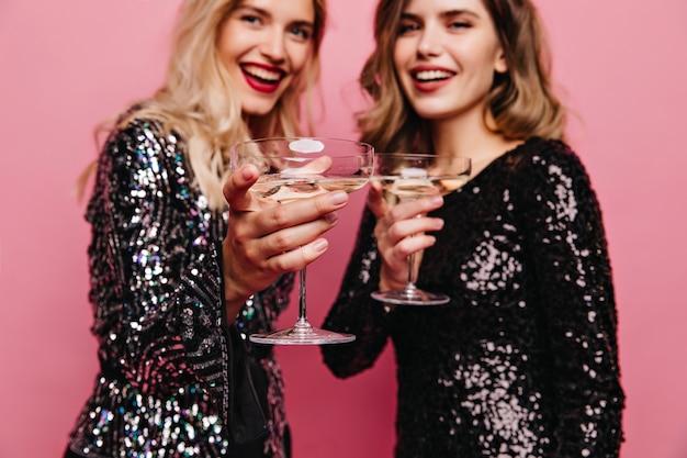 パーティーでポーズをとる黒いドレスを着た至福の白人女性。一緒にワインを飲むきらめきの衣装で喜んでいる女の子。