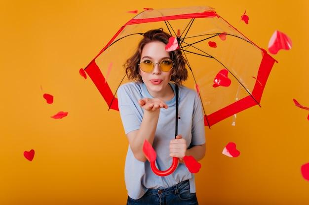 Beata ragazza riccia con gli occhiali che invia un bacio d'aria, in piedi sotto l'ombrello. giovane donna castana felice che posa sulla parete gialla con i cuori rossi dietro.