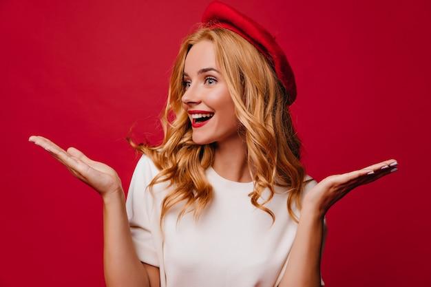 놀란 된 미소로 붉은 벽에 포즈 행복 곱슬 소녀. 경쾌한 금발 모델의 실내 사진.