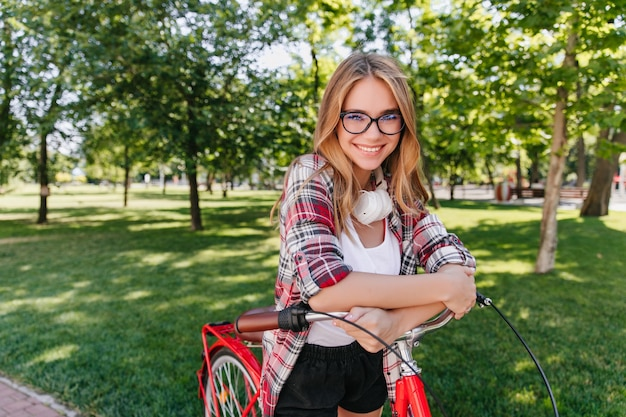 Blissful cute lady with bicycle looking with smile. outdoor shot of gorgeous white girl enjoying weekend in spring.
