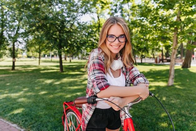 笑顔で見ている自転車と至福のかわいい女性。春の週末を楽しんでいるゴージャスな白人の女の子の屋外ショット。