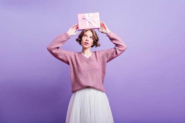 Блаженная европейская женская модель держит подарок на день рождения над головой и улыбается. очаровательная девушка с короткой стрижкой позирует с подарком на цветной стене.