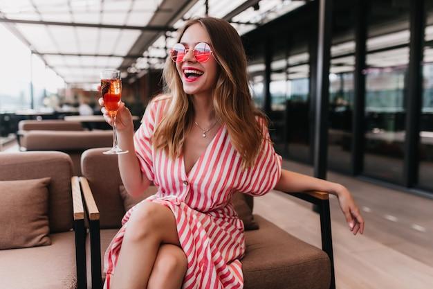 夏の日をレストランで過ごす至福の金髪の女の子。幸せなヨーロッパの女性はシャンパンを飲み、笑顔の縞模様のドレスを着ています。
