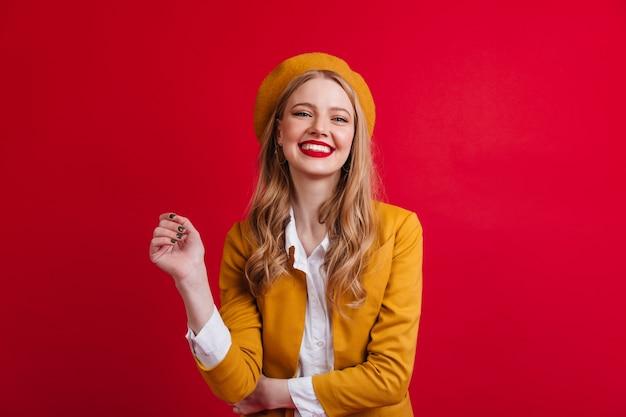 Modello femminile francese beato che ride. vista frontale della ragazza bionda in berretto isolato sulla parete rossa.