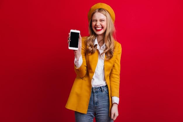 Beata donna francese che tiene smartphone con schermo vuoto. vista frontale della ragazza bionda elegante in berretto isolato sulla parete rossa.