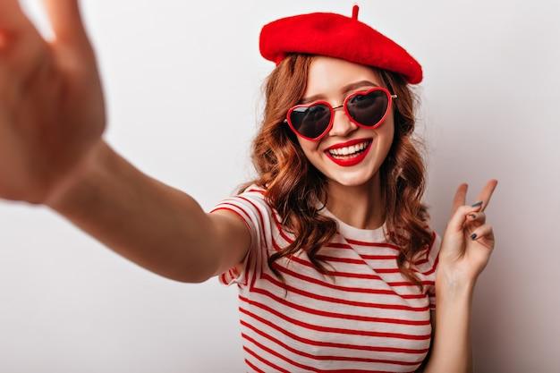 Beata donna francese in occhiali da sole che fanno selfie. ragazza dai capelli rossi riccia entusiasta in posa sulla parete bianca.