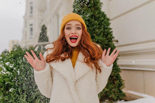 寒い冬の日に楽しんでいる至福の生姜少女。雪でポーズをとる感情的な赤毛の女性。