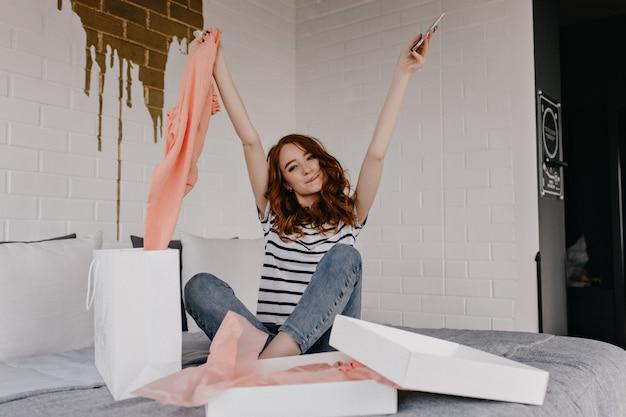 寝室でポーズをとるジーンズの至福の生姜の女の子。ベッドに座っている魅力的な巻き毛の女性の屋内写真。
