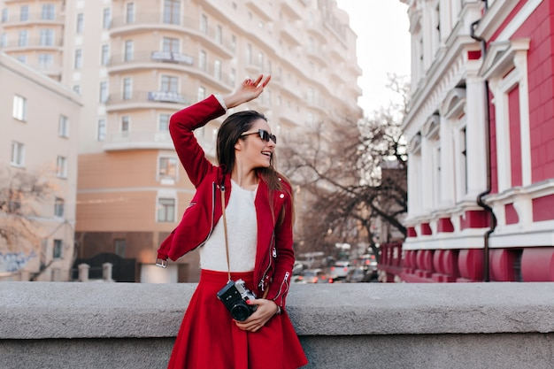 Beata ragazza con gli occhiali che balla per strada dopo il servizio fotografico
