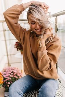 Блаженная девушка в синих джинсах смеется с закрытыми глазами. молодая женщина играет со своими вьющимися волосами.