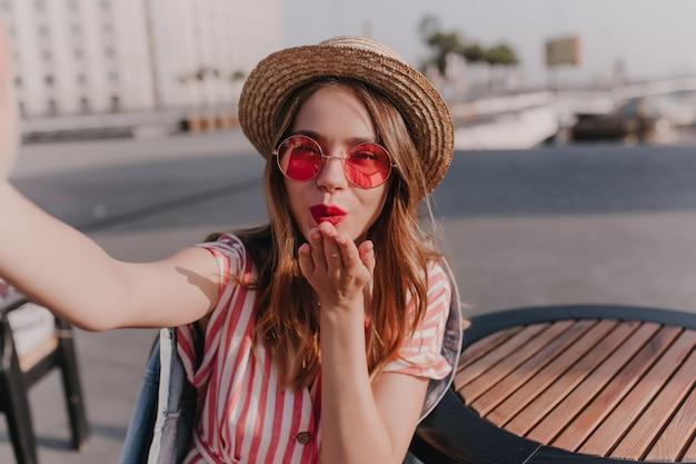 여름 날에 공기 키스를 보내는 트렌디 한 둥근 안경에 행복한 소녀. 도시에 셀카를 만드는 밀짚 모자에 매혹적인 여자의 야외 샷.