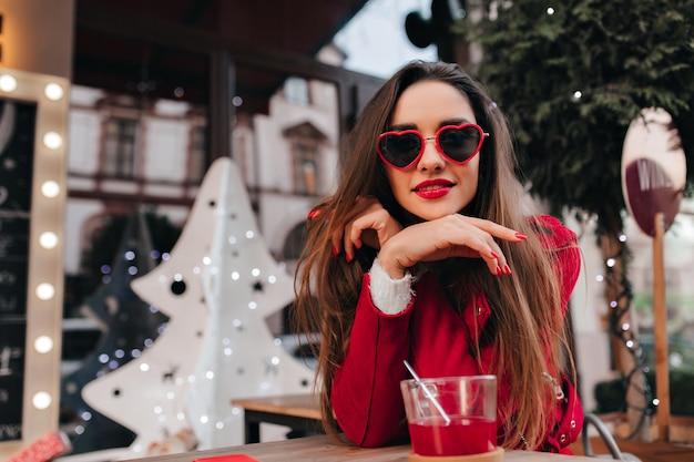 モダンな外観の屋外カフェに座っているスタイリッシュなマニキュアと至福の少女