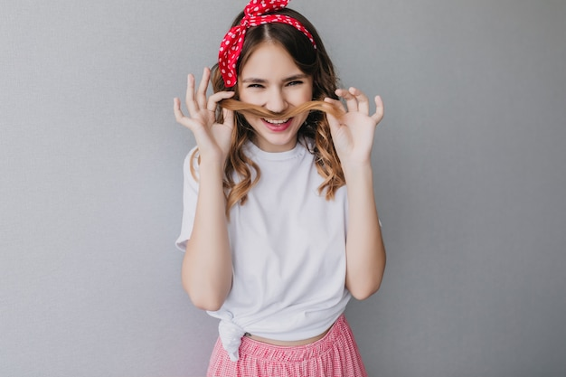 Блаженная девушка с волнистой прической, корча рожи. привлекательная женщина кавказской, играя с ее вьющимися волосами.