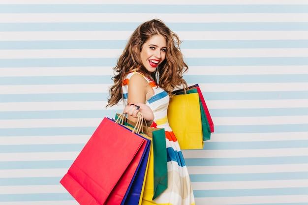 ショッピングを楽しんでいる至福の優雅な女の子。肩越しに見ている店のバッグを持つ嬉しい若い女性の肖像画。