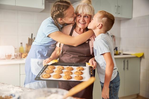 고마운 아이들에게 키스하는 행복한 할머니