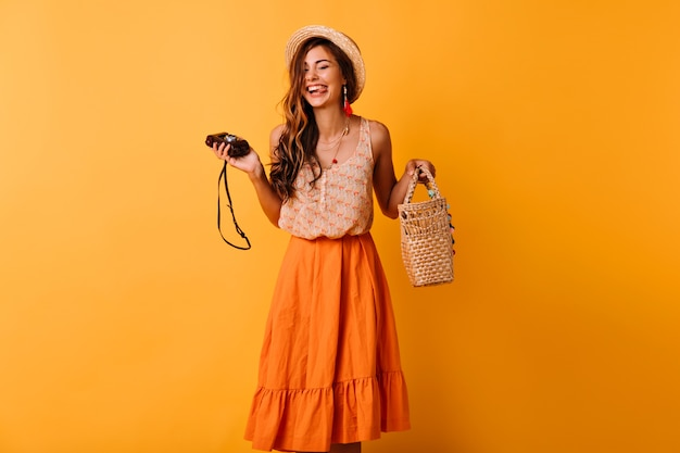 黄色のカメラでポーズをとる流行の夏服の至福の女性。スタジオで身も凍るような帽子をかぶったポジティブな美少女。