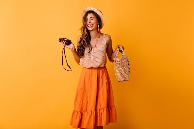 Beata signora in abiti estivi alla moda in posa con la fotocamera su giallo. bella ragazza positiva in cappello agghiacciante in studio.
