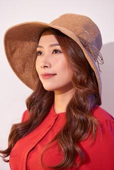 Блаженная дама с широкой улыбкой позирует в солнечный день. смеющаяся девушка в красной одежде и модной соломенной шляпе наслаждается хорошей погодой в выходные.