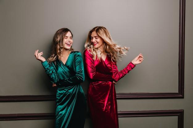 녹색 드레스 친구와 함께 놀 아 요 행복 한 웃는 소녀. 벨벳 옷을 입고 편안한 두 여성의 실내 사진.