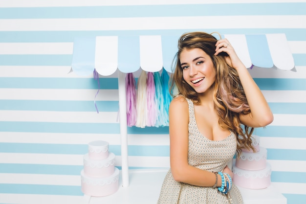 Blissful long-haired girl in trendy vintage dress posing with beautiful smile in front of sweets shop. gorgeous young woman with shiny hair standing beside candy counter  on cute striped wall.