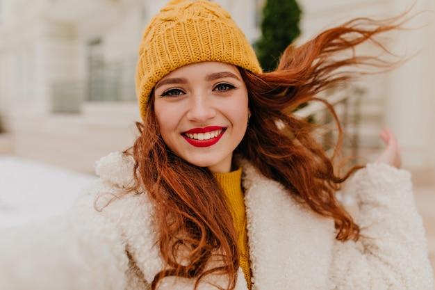 冬の週末に自分撮りをする赤い唇を持つ至福の長い髪の女性。幸せを表現する帽子をかぶった陽気な生姜の女の子。