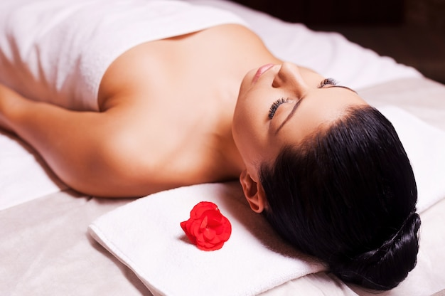 Blissful moments. top view of beautiful young woman wrapped in towel lying on massage table and keeping eyes close