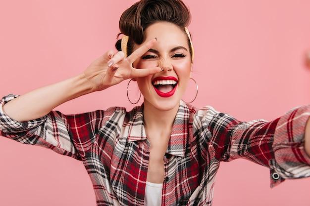 행복 한 핀 업 소녀 분홍색 배경에 평화 기호로 포즈. 체크 무늬 셔츠 selfie 복용 갈색 웃는 아가씨.