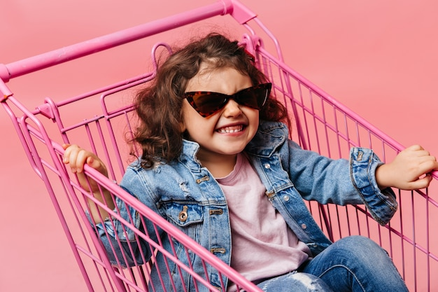 Blissful preschool child sitting in shopping cart. laughing kid in jeans having fun on pink background.
