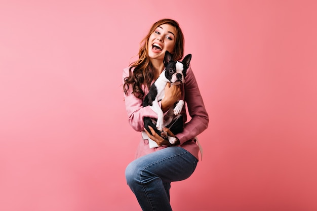 Blissful red-haired lady dancing and holding cute dog. indoor portrait of romantic curly woman expressing positive emotions during portraitshoot with french bulldog.