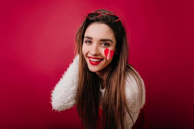 Блаженная романтическая девушка позирует с искренней улыбкой и играет с волосами