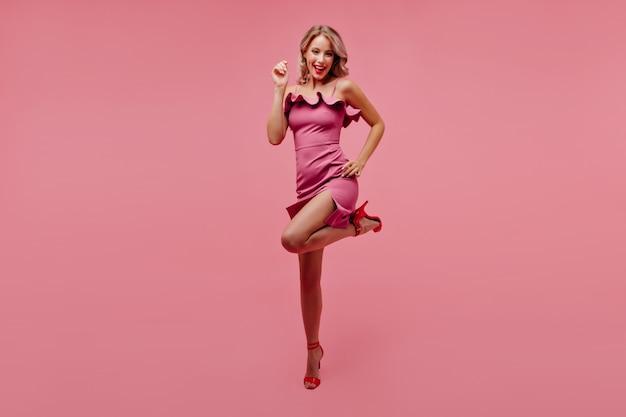 Блаженная стройная женщина смешно танцует в студии с розовым интерьером