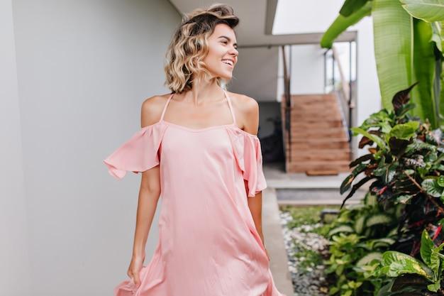 至福の短い髪の少女は、良い一日を楽しんでいるピンクの服を着ています。庭の緑の植物の横を歩いているのんきな白人女性モデルの屋外写真。