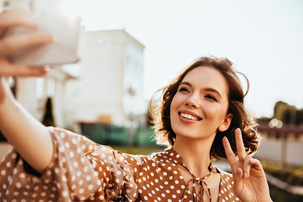 Beata donna dai capelli corti in abiti marroni che esprimono felicità. jocund lady tenendo il telefono e facendo selfie.