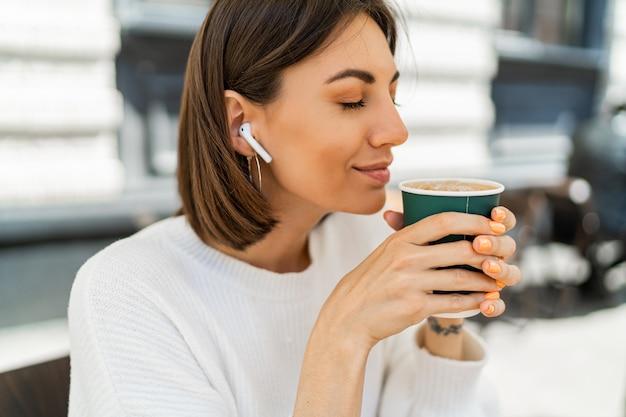 Beata donna dai capelli corti che si gode il cappuccino al bar, indossando un maglione bianco accogliente e ascoltando la musica preferita con gli auricolari