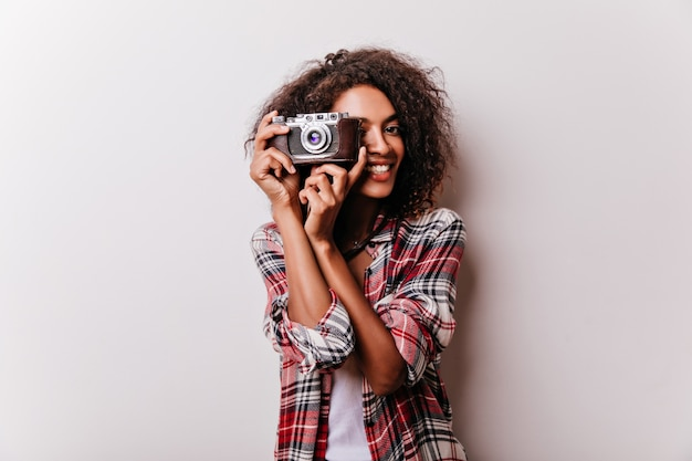 카메라 샷 만드는 행복 웃는 소녀. 여성 촬영 작가의 실내 촬영은 체크 무늬 셔츠를 착용합니다.