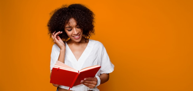 Blissful   smiling  mix race woman  reading with pleasure book  over orange background. copy space for text.