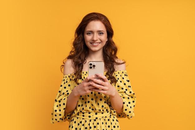 Donna sorridente beata dalla testa rossa che tiene il telefono cellulare in abito estivo giallo in posa sul giallo