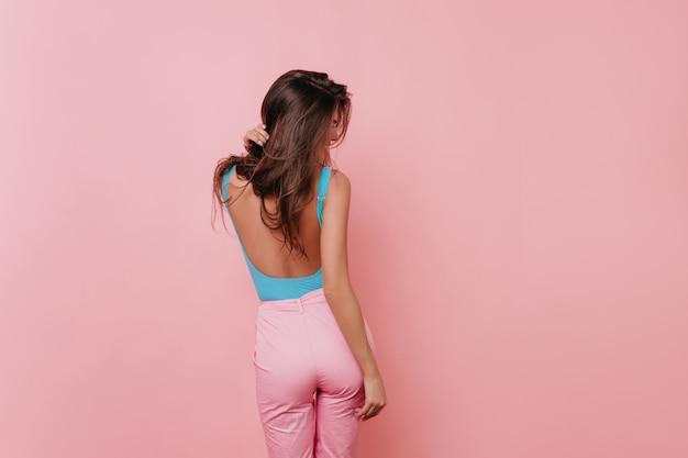 Блаженная загорелая девушка в розовых штанах наслаждается фотосессией в помещении