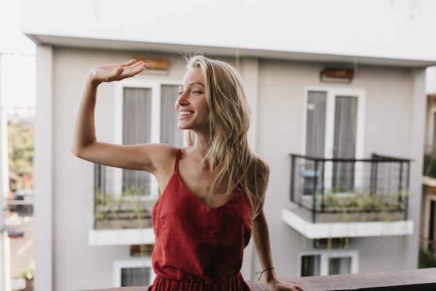 미소로 손을 흔들며 파자마에 행복 무두 질된 여자. 발코니에 서있는 놀라운 백인 여성 모델.