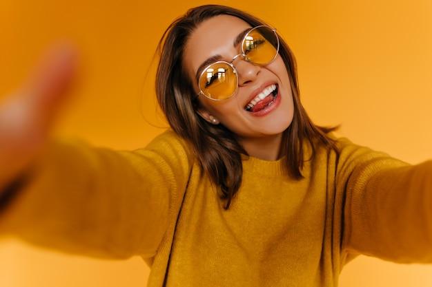 Блаженная загорелая женщина в свитере делает селфи и смеется. жизнерадостная девушка в солнцезащитных очках фотографирует себя на оранжевой стене.