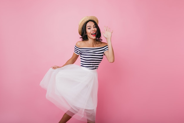 踊りながら手を振る至福の日焼けした女性。満足しているブルネットの少女の屋内肖像画は、エレガントな緑豊かなスカートを着ています。