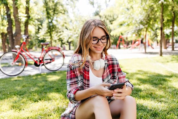 공원에서 전화를 사용하는 행복한 백인 아가씨. 잔디와 문자 메시지에 앉아 캐주얼 안경에 즐거운 유럽 소녀.