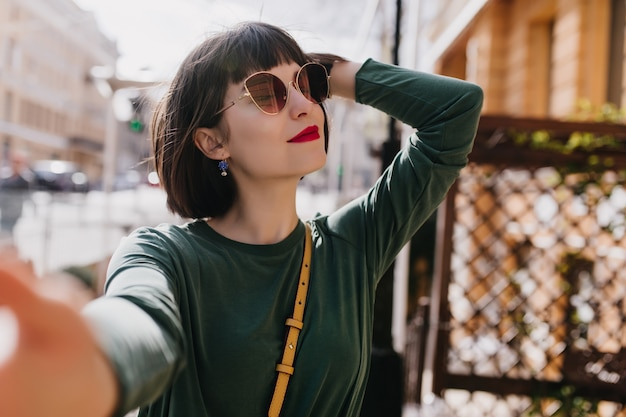 Blissful white woman with short hair making selfie in good spring day. outdoor photo of interested girl in stylish sunglasses and green sweater.