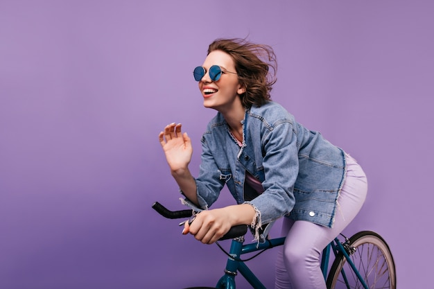 Beata donna in giacca casual in posa sulla bici. emotiva ragazza dai capelli corti in bicchieri scintillanti in sella alla bicicletta.